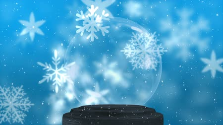 seasons changing : Empty snow globe on blue background with christmas snowflakes falling all around