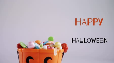 superstition : Animation of the words Happy Halloween written in black and orange, with an orange pumpkin face plastic bucket filled with sweets and piles of sweets in the foreground, against a white background Stock Footage
