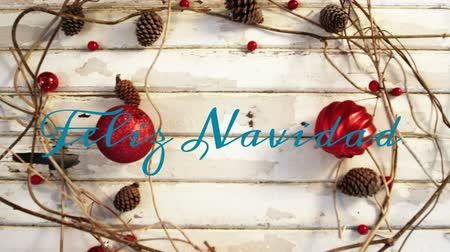 seasons changing : Animation of the words Feliz Navidad written in blue over Christmas decorations with red baubles and pine cones