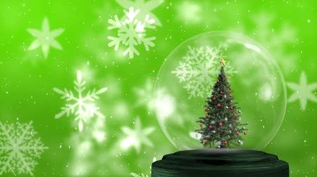 seasons changing : Animation of a decorated Christmas tree in a snow globe, with falling snowflakes against a green background