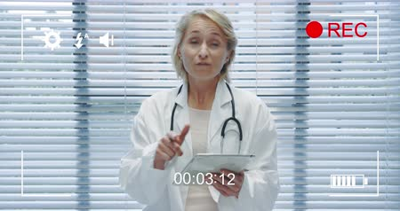 modo : Animation of a portrait of a middle aged Caucasian female doctor looking to camera holding a tablet computer and talking, seen on a screen of a digital camera in record mode with icons and timer 4k