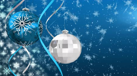seasons changing : Animation of snow falling and Christmas decorations with white and blue baubles on blue background