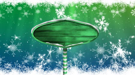 seasons changing : Animation of snowflakes falling and green wooden sign board on green to blue background Stock Footage