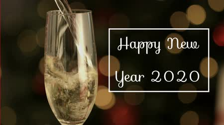 flet : Animation of the words Happy New Year 2020 written in white in white frame over champagne flute and glowing lights Wideo