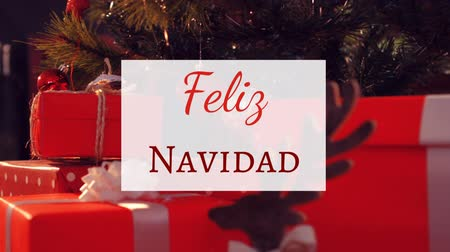Навидад : Animation of the words Feliz Navidad written in red on white sign over Christmas tree and presents in the background