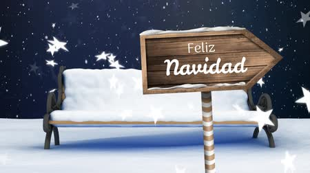 Навидад : Animation of the words Feliz Navidad written in white on red wooden arrow sign board with snowflakes and stars falling and snow covered bench on blue background Стоковые видеозаписи