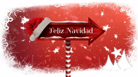 Навидад : Animation of the words Feliz Navidad written in white on red wooden arrow sign board with snowflakes and stars falling and santa hat on red background Стоковые видеозаписи