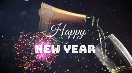 flet : Animation of the words Happy New Year written in white over champagne being poured to champagne flute and firework display