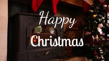 Навидад : Animation of the words Happy Christmas written in white over fireplace at Christmas time and Christmas tree and Christmas stockings Стоковые видеозаписи