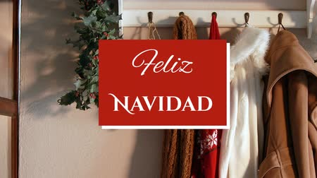 Навидад : Animation of the words Feliz Navidad written in white on red square over Christmas decorations with Christmas stockings and mistletoe in the background