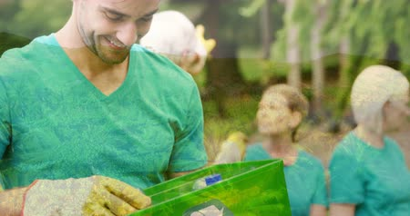 geri dönüşümlü : Animation of a young Caucasian man holding a green box with recycling sign smiling to camera with a group of people in the background and countryside in the foreground 4k