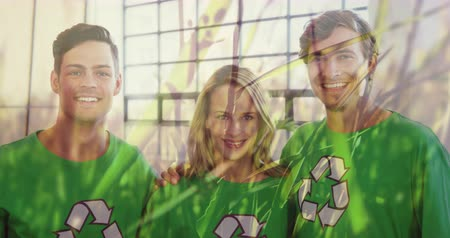 geri dönüşümlü : Animation of a group of young Caucasian male and female friends wearing green t-shirts with recycling sign, embracing, smiling and giving thumbs up with grass moving in the foreground 4k Stok Video