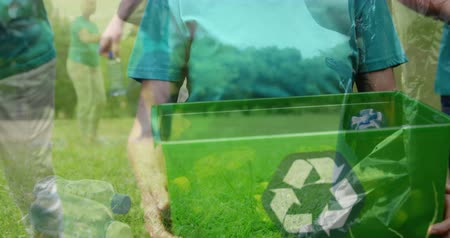 biodegradable : Animation of a smiling young Caucasian woman holding a green box with recycling sign while a group of people putting plastic bottles in the box in the garden with countryside in the foreground 4k Stock Footage