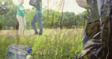 klíring : Animation of a young Caucasian man collecting plastic bottles into a black bin bag with two people cleaning a garden in the background with moving countryside in the foreground 4k