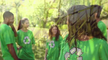 planety : Animation of a group of young mixed race male and female friends wearing green t-shirts with recycling sign, smiling and giving thumbs up with grass moving in the foreground