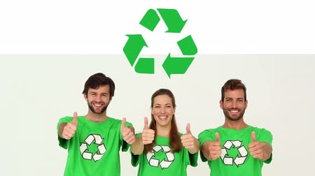 biodegradable : Animation of a group of young multi-ethnic male and female friends wearing green t-shirts with recycling sign, smiling and giving thumbs up with recycling sign on white background
