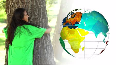 biodegradable : Animation of a young mixed race woman wearing a green t-shirt with recycling sign, hugging a tree and giving thumbs up with globe spinning next to her Stock Footage