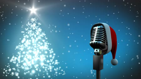 seasons changing : Animation of a retro silver microphone with Santa hat and rotating Christmas tree on blue background Stock Footage