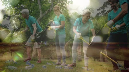 changing : Animation of a group of people collecting plastic bottles and putting them into black bin bag, raking lawn with moving spots of light in the foreground Stock Footage