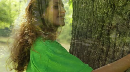 biodegradable : Animation of a young Caucasian woman wearing a green t-shirt, hugging a tree and smiling with countryside in the foreground