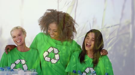geri dönüşümlü : Animation of three young multi-ethnic female friends wearing green t-shirts with recycling sign, embracing, holding a box with recycled plastic bottles and smiling with grass moving in the foreground