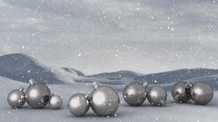 seasons changing : Animation of winter scenery with snow falling and Christmas decorations with silver baubles and countryside in the background