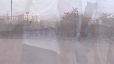 pace : Animation of commuters passing on busy city street in fast motion with cityscape in the background
