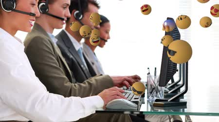 emoticon : Animation of emoji icons flying from right to left with four young multi-ethnic coworkers working in call centre in the background
