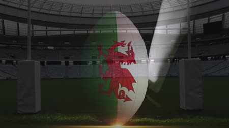 ウェールズ : Animation of rugby ball with Welsh flag on being kicked by a rugby player at a stadium
