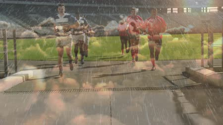 zift : Animation of rugby players running off a pitch at a sports stadium with rain and clouds in the foreground Stok Video