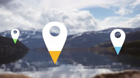 wijzer : Animation of location pins filling up with yellow, blue and green color over cloudt sky and mountain landscape in the background Stockvideo