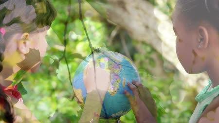 environmental awareness : Animation of two girls using globe at school with trees in the foreground