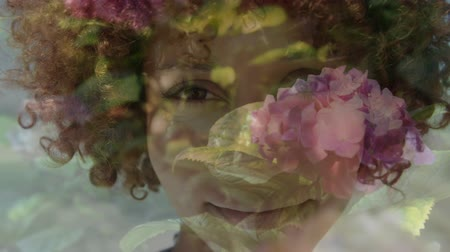 odpowiedzialność : Animation of young mixed race woman smiling to camera with flowers in the foreground