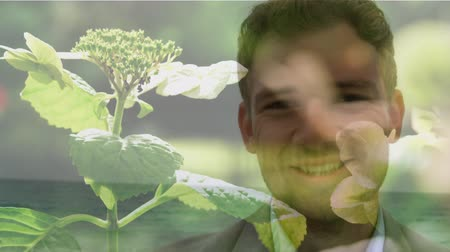 odpowiedzialność : Animation of young Caucasian man smiling to camera with flowers in the foreground