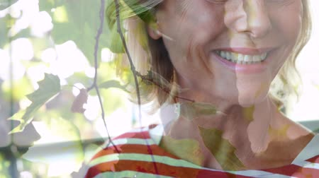 sustainable resources : Animation of happy Caucasian woman smiling to camera with tree in the foreground Stock Footage