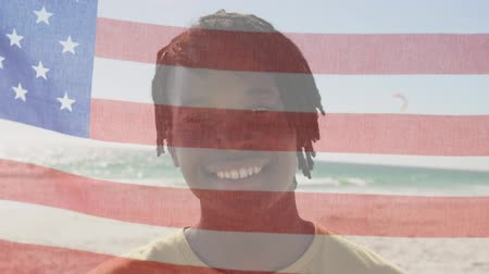 благодарение : Animation of young mixed race man looking to camera with American flag waving in the foreground