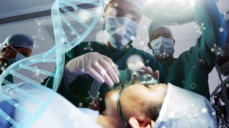 genen : Animation of DNA strand spinning over surgeons in the operating theatre Stockvideo