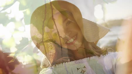sunhat : Animation of young Caucasian woman smiling to camera with tree in the foreground