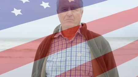 spangled : Animation of Caucasian man looking to camera with American flag waving in the foreground Stock Footage