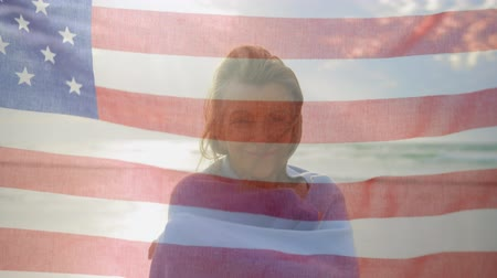 spangled : Animation of Caucasian woman smiling to camera with American flag waving in the foreground Stock Footage