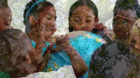 ślady stóp : Animation of multi-ethnic school children using globe at school with trees in the foreground