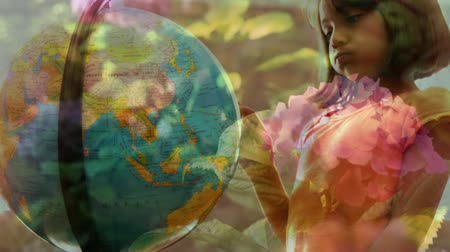 bolygók : Animation of mixed race schoolgirl using globe at school with flowers in the foreground