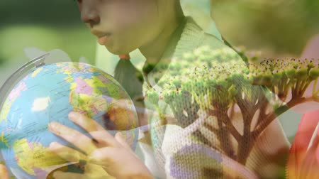 bolygók : Animation of schoolboy and schoolgirl using globe at school with flowers in the foreground