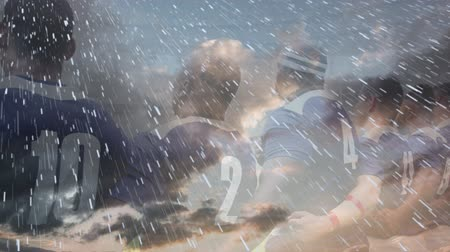 marş : Animation of rugby players embracing and singing anthem before the match at a stadium with clouds and snow in the foreground Stok Video