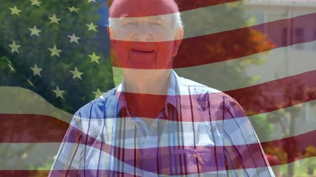 old glory : Animation of Caucasian man smiling to camera in a park with American flag waving in the foreground Stock Footage