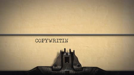 コミットメント : Animation of a close up of the type guard and moving type bars of a typewriter, typing out the word Copywriting on cream coloured paper