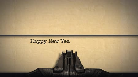 impressão digital : Animation of a close up of the type guard and moving type bars of a typewriter, typing out the words Happy New Year in upper and lower case letters on cream coloured paper Stock Footage