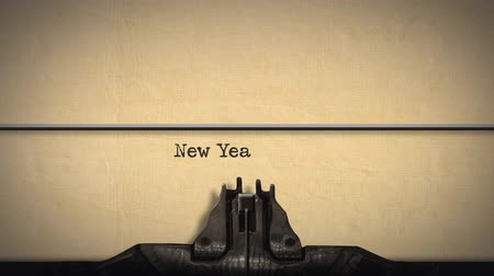 impressão digital : Animation of a close up of the type guard and moving type bars of a typewriter, typing out the words New Year in upper and lower case letters on cream coloured paper