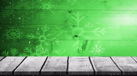 szenteste : Animation of winter scenery with snowflakes falling and wooden boards on a green background Stock mozgókép
