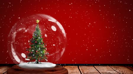 snow globe : Animation of Christmas snow globe with Christmas tree inside and snow falling on red background